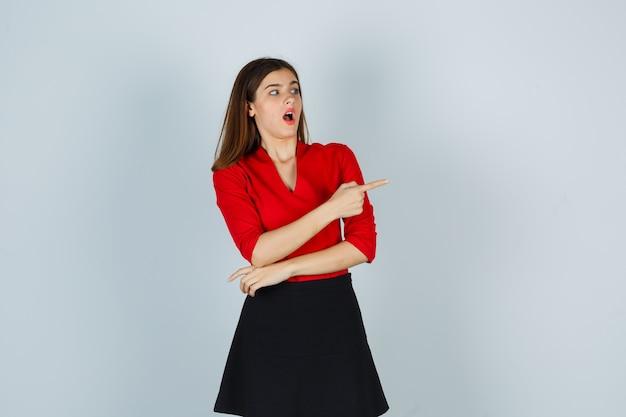 赤いブラウス、黒いスカートで人差し指で右を指し、驚いて見える若い女性