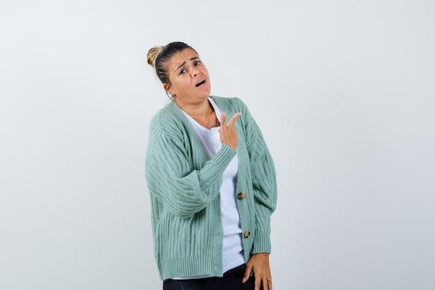 Giovane donna che punta a destra con il dito indice in camicia bianca e cardigan verde menta e sembra tormentata