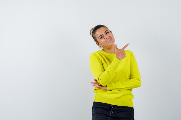 Giovane donna che punta a destra con il dito indice in maglione giallo e pantaloni neri e sembra felice