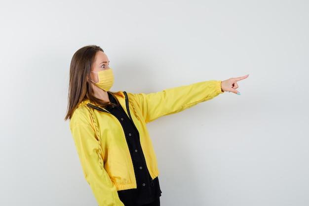 Giovane donna che punta a destra con il dito indice