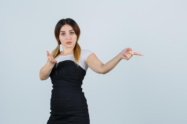 Молодая женщина, указывая вправо указательным пальцем