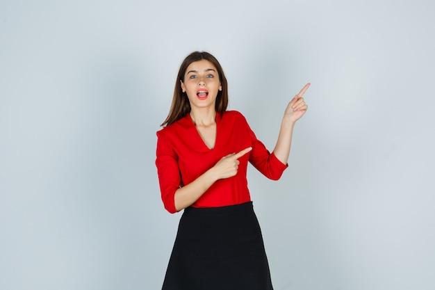 Молодая женщина, указывая вправо указательными пальцами в красной блузке