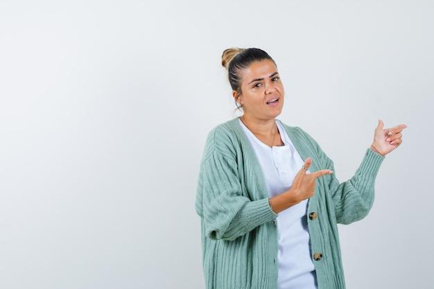 흰색 셔츠와 민트 그린 카디건에 검지 손가락으로 오른쪽을 가리키고 행복해 보이는 젊은 여성
