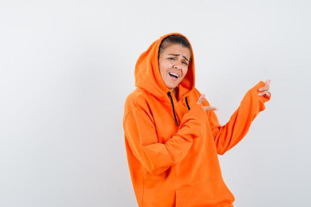 Giovane donna che punta a destra con l'indice in felpa con cappuccio arancione e sembra felice