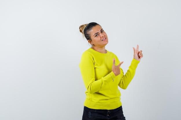 Giovane donna che punta a destra con l'indice in maglione giallo e pantaloni neri e sembra felice