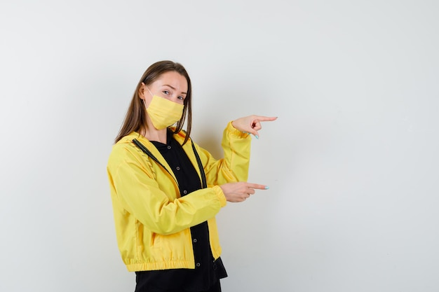Young woman pointing right with index fingers