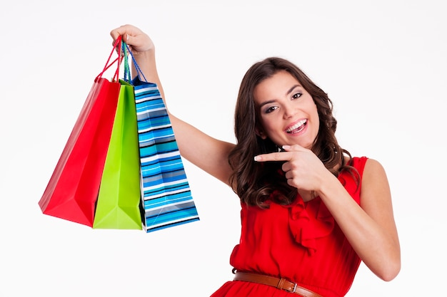 Young woman pointing to shopping bags