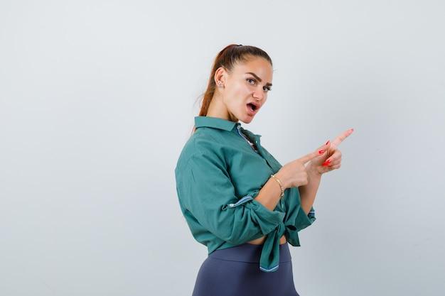 緑のシャツを着てまっすぐ前を指して、不思議に思っている若い女性。 。