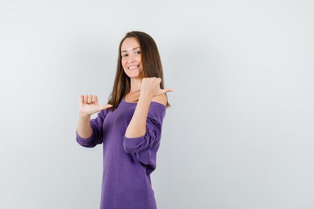 Молодая женщина указывая большими пальцами руки назад в фиолетовой рубашке и выглядела счастливой. передний план.