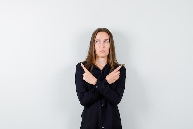 Молодая женщина, указывая в обе стороны