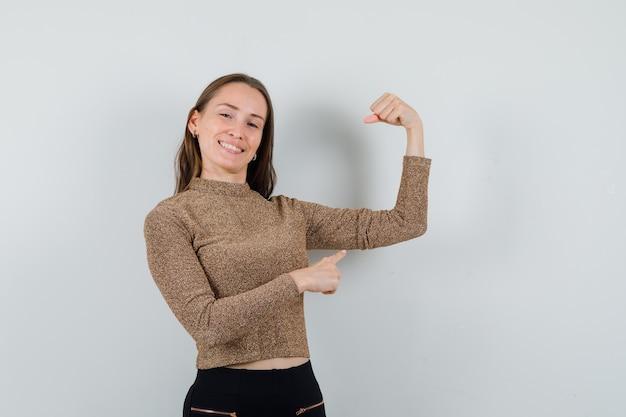 Молодая женщина, указывая на ее мышцу руки в золотой блузке и уверенно глядя, вид спереди.