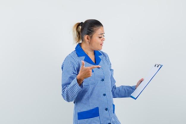 파란색 깅엄 파자마 셔츠에 검지 손가락으로 노트북을 가리키고 예쁜 찾고 젊은 여자. 전면보기.
