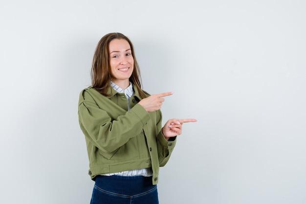 シャツ、ジャケットの右側を指して、楽観的な正面図を探している若い女性。