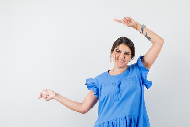 青いドレスを着て横を指して希望に満ちた若い女性