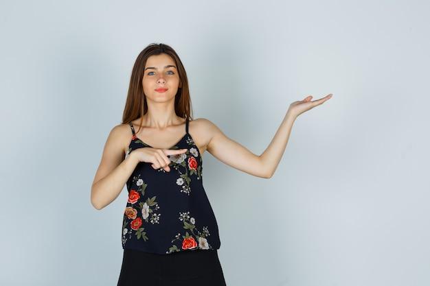 横を指して、花のトップに手のひらを広げて魅力的に見える若い女性