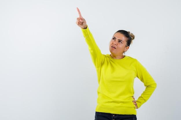 Молодая женщина показывает вверх и держит руку на талии в желтом свитере и черных брюках и выглядит сосредоточенной