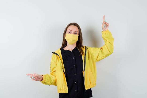 Молодая женщина, указывая вверх и влево указательными пальцами