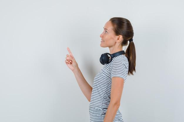 Tシャツ、ヘッドフォンで上向きと笑顔の若い女性。