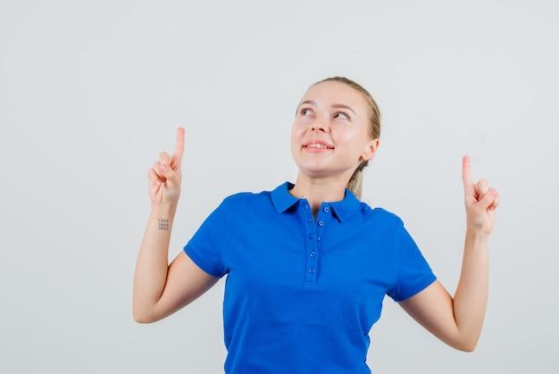 Giovane donna rivolta verso l'alto in maglietta blu e guardando allegra