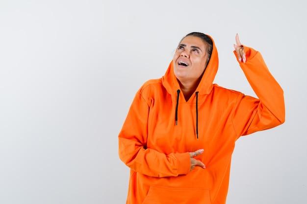 Giovane donna che punta verso l'alto e tiene la mano sulla pancia in felpa con cappuccio arancione e sembra felice