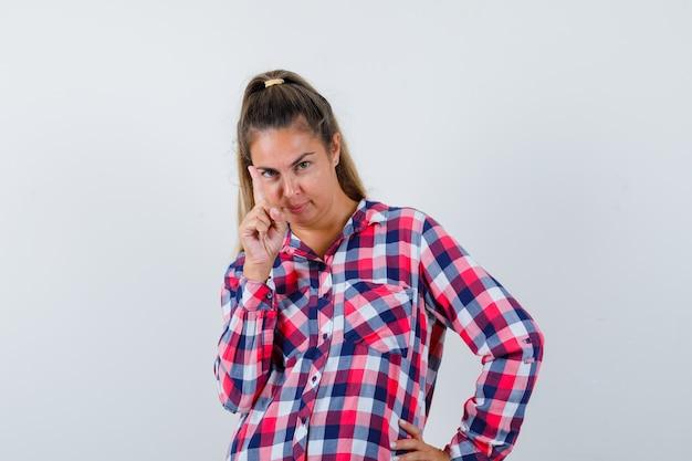 Молодая женщина, указывая вверх в повседневной рубашке и выглядящая умной, вид спереди.