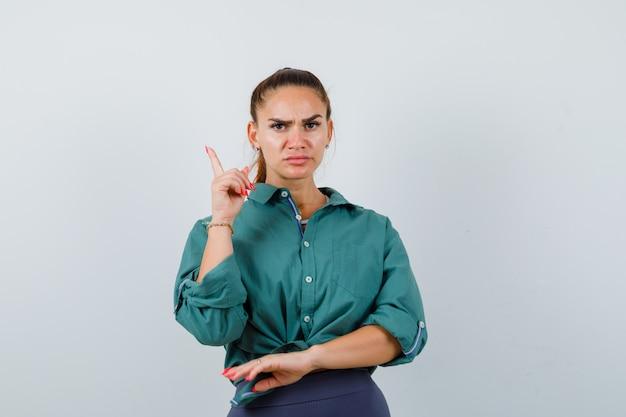 緑のシャツを着て、毅然とした表情で若い女性。正面図。