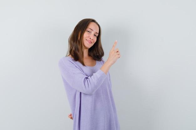 Молодая женщина указывая вверх в сиреневой блузке и выглядит уверенно