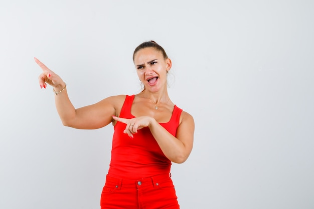 赤いタンクトップ、ズボン、おかしい、正面図で上向きの若い女性。
