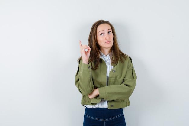 シャツ、ジャケットで上向きになり、躊躇している若い女性。正面図。