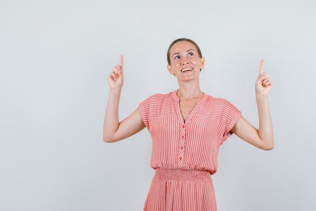 Молодая женщина, указывая вверх в полосатом платье и глядя с надеждой. передний план.