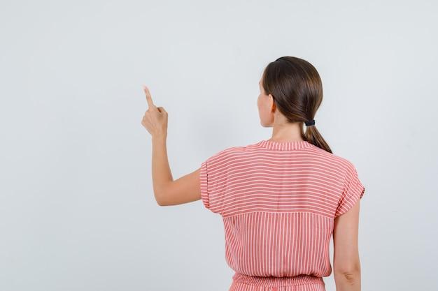 Молодая женщина, указывая вверх в полосатом платье вид сзади.