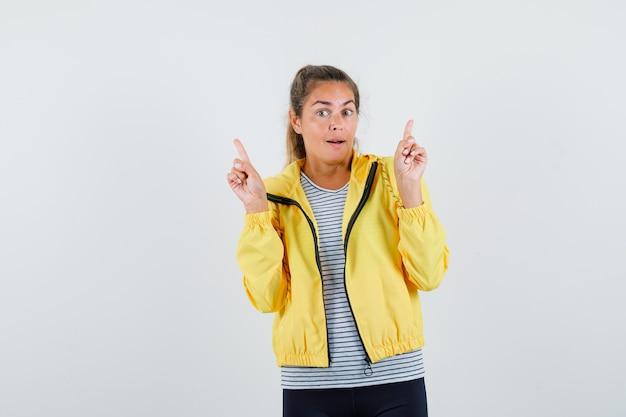 Tシャツ、ジャケットで上向きに、驚いて見える若い女性。正面図。