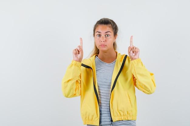 Tシャツ、ジャケットで上向きで物思いにふける若い女性。正面図。