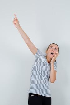 Молодая женщина указывая вверх в футболке, штанах и выглядела испуганной. передний план.