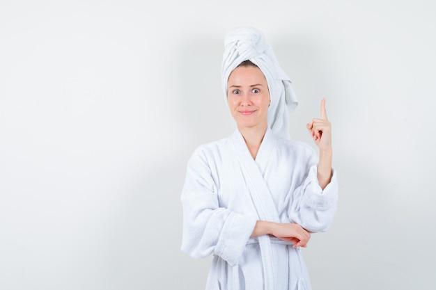 白いバスローブ、タオルで上向きに、陽気に見える若い女性、正面図。