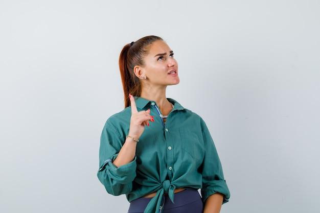 若い女性が上向き、緑のシャツを着て上向きに見て、心配そうに見える、正面図。