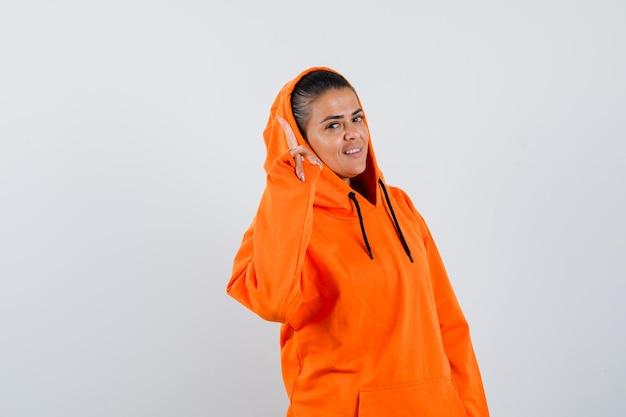 Giovane donna che punta in alto in felpa con cappuccio arancione e sembra bellissima