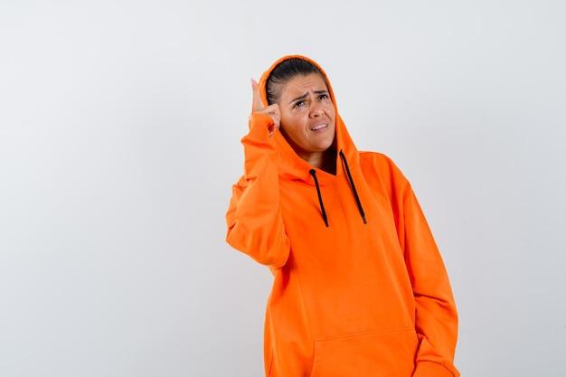 Giovane donna che indica in su in felpa con cappuccio arancione e sembra seria