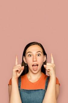 Giovane donna che indica in su con espressione sorpresa