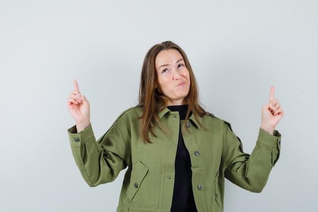 Giovane donna rivolta verso l'alto mentre fa il broncio le labbra in vista frontale giacca verde.