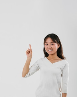 Young woman pointing up with copy space