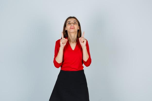 赤いブラウス、黒いスカート、幸せそうに見える人差し指で上向きの若い女性
