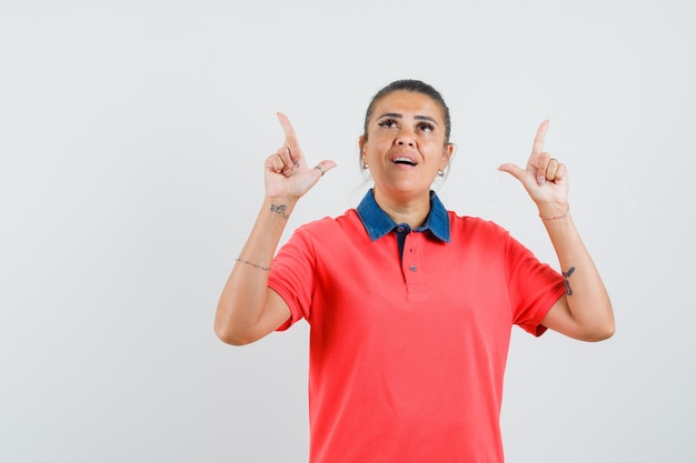 Giovane donna rivolta verso l'alto con il dito indice in maglietta rossa e guardando sorpreso, vista frontale.