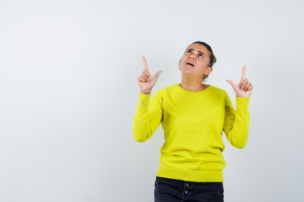 Giovane donna che punta in alto in maglione giallo e pantaloni neri e sembra concentrata Foto Gratuite