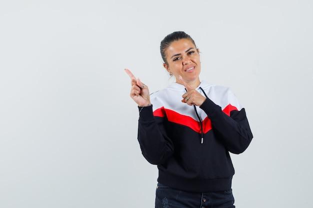 Giovane donna che punta in alto a sinistra con le dita indice in maglione e jeans neri e sembra felice, vista frontale.