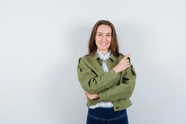 Giovane donna che indica nell'angolo in alto a destra in camicia, giacca e guardando fiducioso, vista frontale.