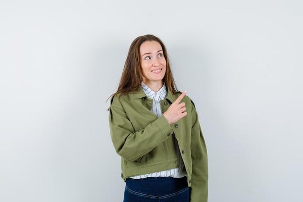 Giovane donna che punta all'angolo in alto a destra in camicia, giacca e sembra sognante. vista frontale.