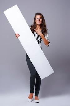 Giovane donna che punta sul tabellone per le affissioni bianco