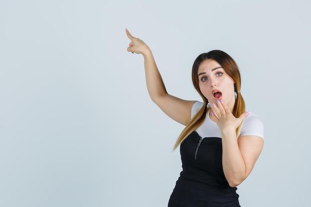Giovane donna che indica con il dito indice mentre tiene la mano sul mento