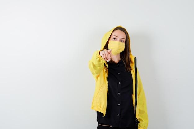Giovane donna che indica con il dito indice